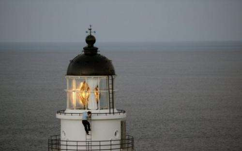 A Taiwanese government employee inspects a lighthouse at Santiaochiao, on July 11, 2013