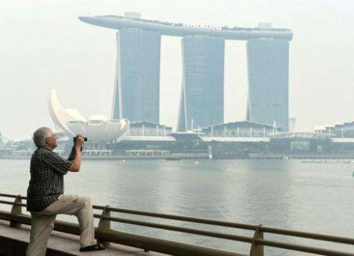 A tourist takes pictures in front of the Marina Bay Sands hotel in Singapore, on June 17, 2013