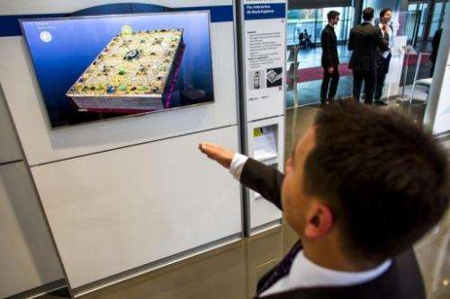 A visitor tests an interactive 3-D boook explorer at the 2013 CeBIT technology trade fair in Hanover, on March 5, 2013
