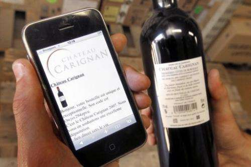 A wine-drinker checks the tracking of a wine bottle on his smart phone, western Frane, June 6, 2010