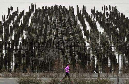 A woman jogs past an old pier along the Hudson River in New York on January 10, 2013