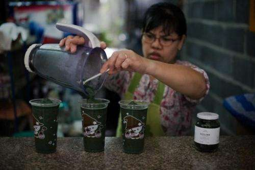 A woman prepares a spirulina shake in Bangkok on June 24, 2013