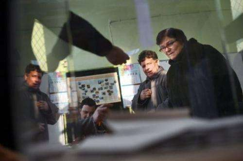 A woman receives a ballot at a polling station during the national referendum in the town of Belene on January 27, 2013