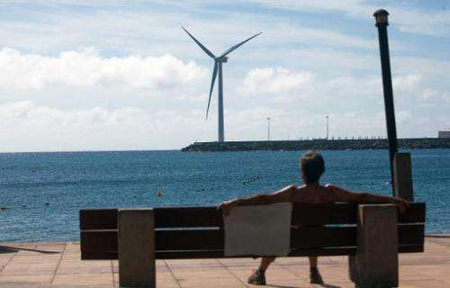 A woman sits on a bench backdropped by Spain's largest wind turbine. in the port of Arinaga, on Gran Canaria in the Spanish arch