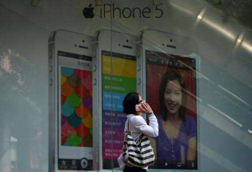 A woman uses a mobile phone as she walks past an Apple iPhone 5 poster outside a store in Beijing on September 11, 2013