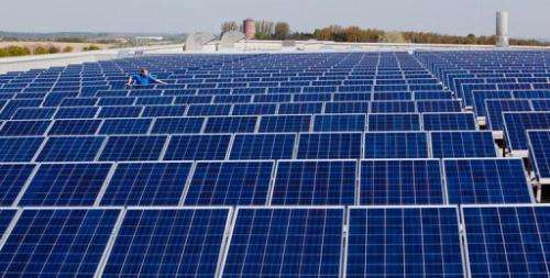 A worker checks solar panels on the roof of Conergy's solar panel plant in Frankfurt an der Oder on April 22, 2009