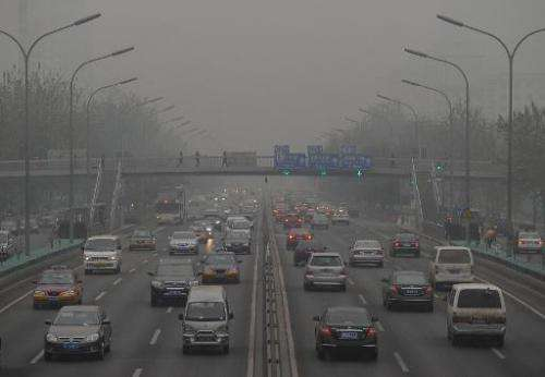 Cars travel through a haze of pollution in Beijing on December 5, 2011