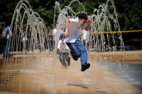 Children play in a water fountain to cool down in Medellin, Antioquia, Colombia in September 11, 2009