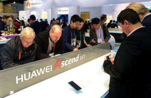 Consumers look at products at the Huawei booth at CES in Las Vegas on January 10, 2013