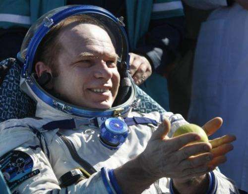 Cosmonaut Oleg Kotov holds an apple after the landing of a Russian Soyuz space capsule near Dzhezkazgan on June 2, 2010