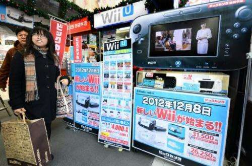Customers walk past a console display at an electronics shop in Tokyo, on December 8, 2012