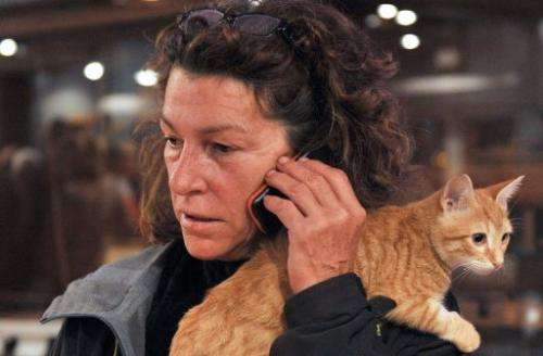 French yachtswoman Florence Arthaud makes a call with her cat on her shoulder in Marseille on October 31, 2011