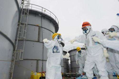 Fukushima Governor Yuhei Sato (orange helmet) inspects the contaminated water tanks at Tokyo Electric Power Co (TEPCO) Fukushima