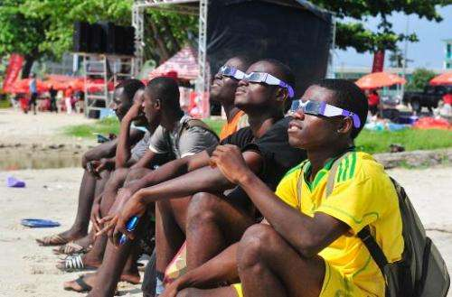 Gabonese people look at a rare solar eclipse through special glasses, on November 3, 2013 in Libreville