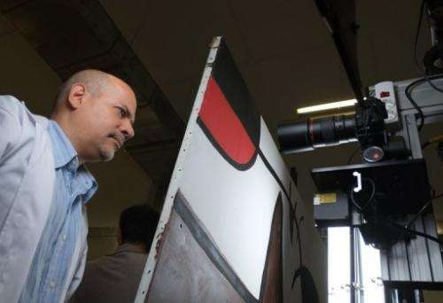 Humberto Duran of Reina Sofia Museum in Madrid monitors a robot taking pictures of a Miro painting on July 4, 2013
