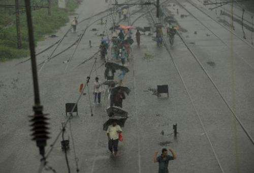 Indians walk along flooded railroad tracks during rain showers in Mumbai on July 23, 2013