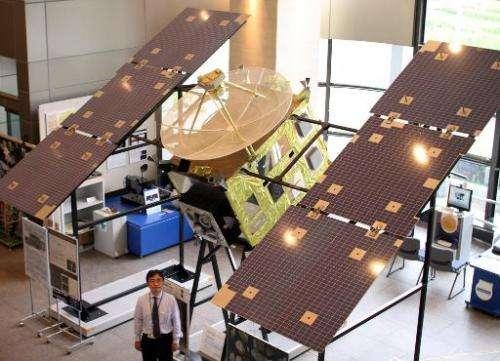 Japan Aerospace Exploration Agency (JAXA) associated professor Makoto Yoshikawa displays the full-scale model of Japan's space p