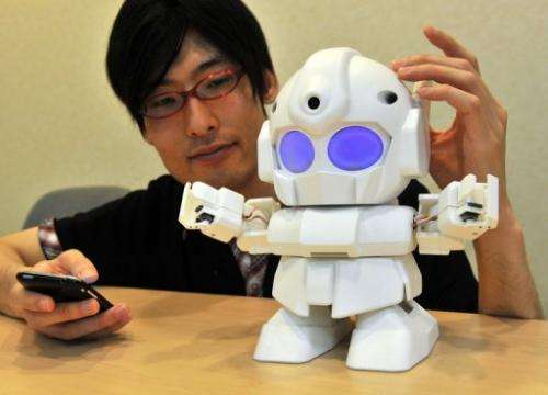 "Japanese engineer Shota Ishiwatari displays the robot ""Rapiro"" which works with a ""Raspberry Pi"" in Tokyo, J"