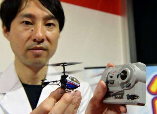 "Japan's toy maker CCP employee shows a toy helicopter, ""Nano-Falcon,"" in Tokyo, on June 13, 2013"