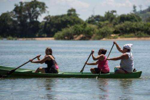 Local women paddle on a canoe across the Xingu river in northern Brazil, on August 7, 2013