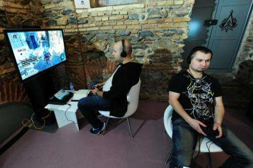 Men play Assassin's Creed on September 29, 2011, in Istanbul