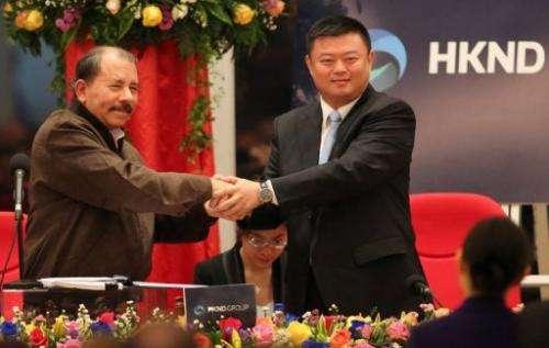 Nicaraguan President Daniel Ortega (L) shake hands with Wang Jing, president of HKND Group in Managua, on June 14, 2013