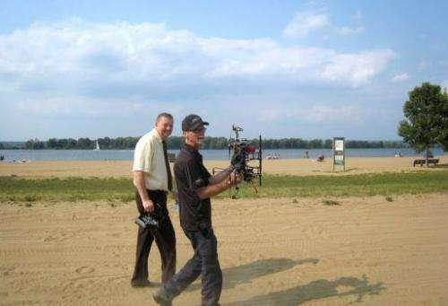 Ottawa city councilor Bob Monette (L) and hexacopter owner Steve Wambolt walk at Petrie Island beach