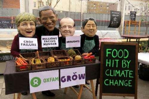 Oxfam protesters wear masks depicting (from left) German Chancellor Angela Merkel, US President Barack Obama, French President F