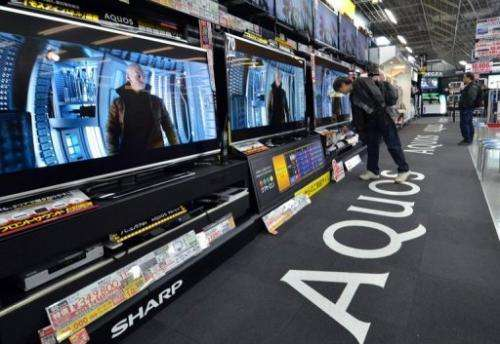 People check out TV sets by Japanese electronics maker Sharp at an electronics shop in Tokyo, on March 6, 2013