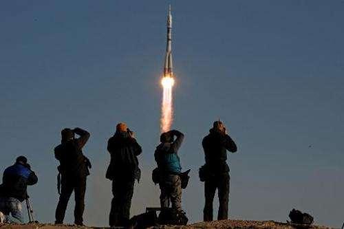 People take photographs as a Soyuz spacecraft carrying Japanese astronaut Koichi Wakata, Russian cosmonaut Mikhail Tyurin, US as