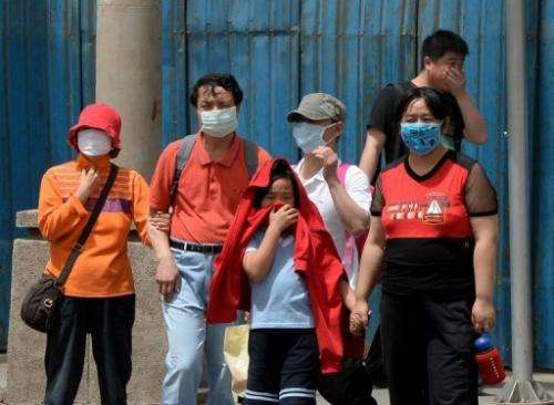 People wear masks to protect against air pollution and dust in Beijing on May 19, 2013