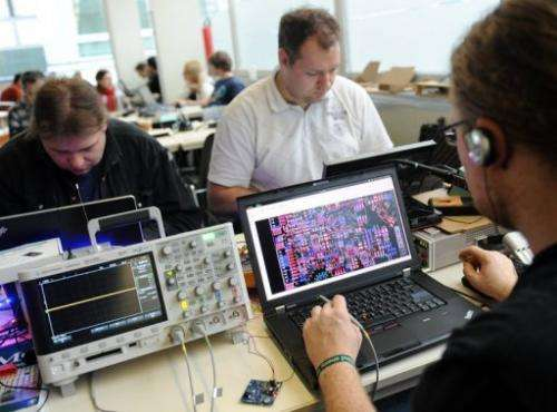 People work on their laptops during an IT convention in Berlin, on December 27, 2011