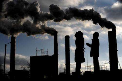 Polish women speak backrounded by of power plant chimneys in Patnow, east of Poznan on December 2, 2008