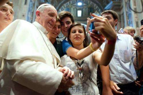 Pope Francis poses with young people in the Church of Saint Augustine in Rome on August 28, 2013