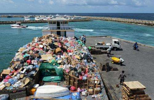 Residents of Male, the capital of the Maldives, unload trash that will be put on a boat that ferries the refuse from the the cap
