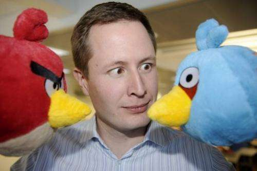 """Rovio CEO Mikael Hed poses with  two """"Angry Bird"""" characters at the company premises in Espoo on January 21, 2011"""