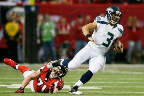 Russell Wilson of the Seattle Seahawks escapes the tackle of Kroy Biermann of the Atlanta Falcons on January 13, 2013