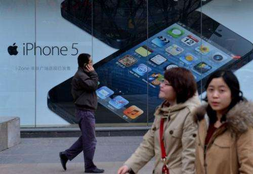 Shoppers walk past an advertisement for the Apple iPhone in Beijing on March 18, 2013