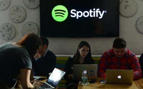 Social media journalists work as Spotify founder and CEO Daniel Ek addresses a press conference in New York, December 11, 2013