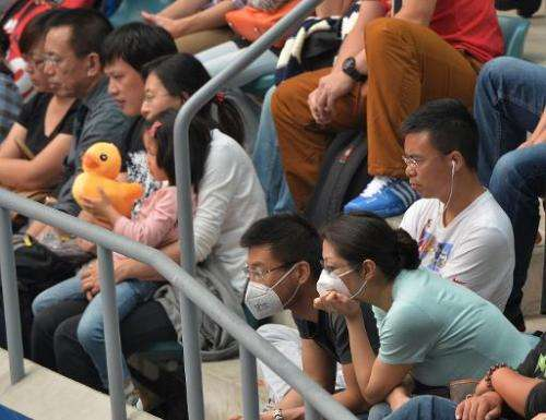 Tennis fans wear face masks during hazardous air pollution as they watch the women's singles semi-finals match at the China Open
