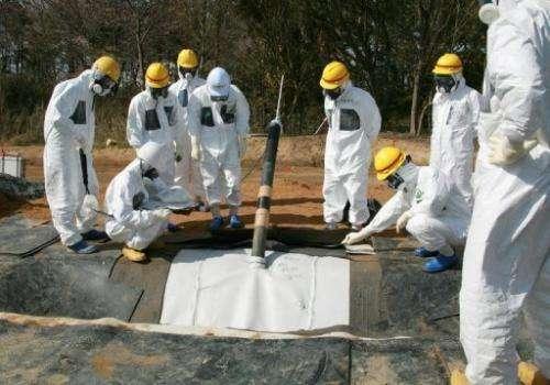 TEPCO officials inspect radioactive reservoirs at the Fukushima Dai-Ichi facility in Okuma, on April 13, 2013.
