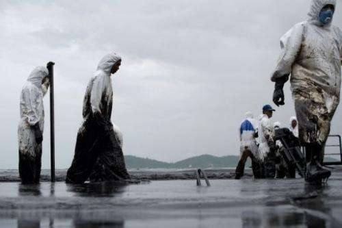 Thai Royal Navy personnel clean Ao Phrao beach on the island of Ko Samet after a major oil slick on July 30, 2013