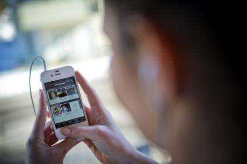 This photo illustration shows a woman using the iPhone application of Swedish music streaming service Spotify.