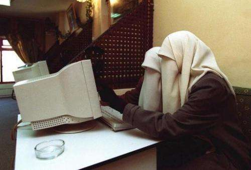 Two Jordanian university students surf the web at an internet cafe in Irbid, on January 23, 2001