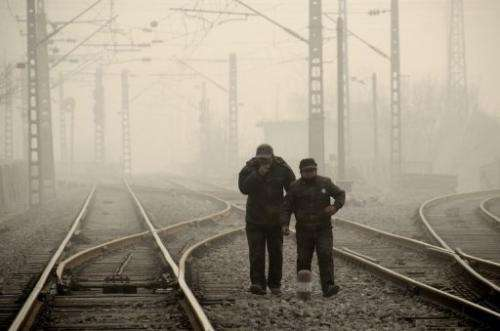 Two men walk along a railway line during smoggy weather in Beijing on January 12, 2013
