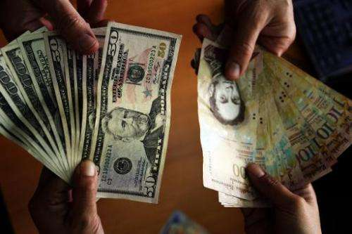 US dollar and Venezuelan Bolivares notes pictured in Caracas on July 16, 2013