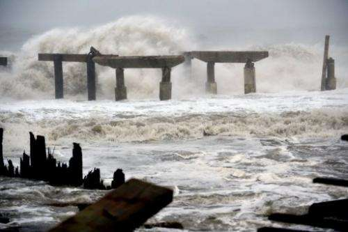 Waves crash against a pier before landfall of Hurricane Sandy on October 29, 2012 in Atlantic City, New Jersey
