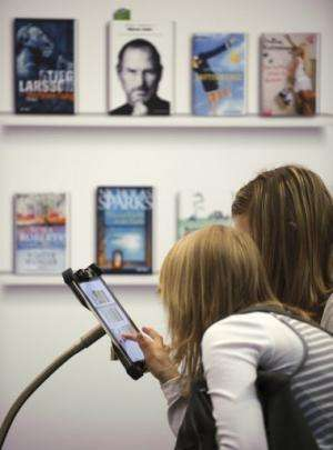 Women try out Deutsche Telekom's PagePlace eBook reader app at the Leipzig Book Fair on March 15, 2012
