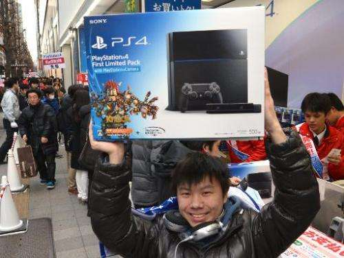 A customer holds up a Sony PlayStation 4 video game console after buying it in Tokyo on February 22, 2014