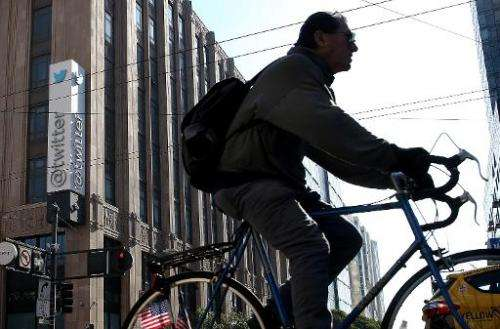 A cyclist rides past the Twitter headquarters in San Francisco on October 25, 2013